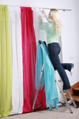 Junge Frau steht auf Leiter und hängt Vorhänge auf