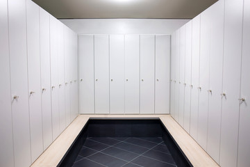 Gym dressing room with lots of white lockers