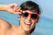 Playful happy woman with red glasses on the beach