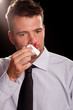 Businessman with a nosebleed. Wiping his nose.