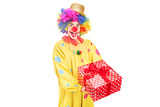 A happy male clown holding a red present
