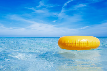 floating yellow ring on crystal blue sea water with sky, shallow