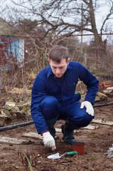 Young man planting winter garlic