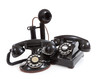 A group of vintage telephones on a white background