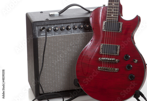 An electric guitar with a black amp on  a white background