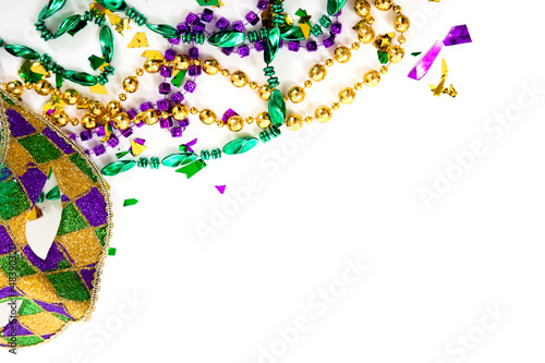 A Mardi gras mask and beads on a white background with copy spac - 48390320