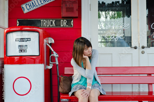 Cute Thai girl is waiting on the bench