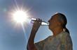 Alte Frau trinkt Mineralwasser an einem heißen Tag