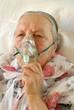 Seniorin atmet Sauerstoff ein durch eine Maske