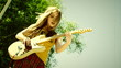 Young woman playing electric guitar outdoors. Old movie.