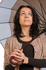 Beautiul brunette sheltering under her umbrella
