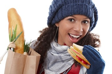 Attractive female biting sandwich at wintertime