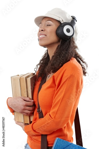 Casual student with earphones and books