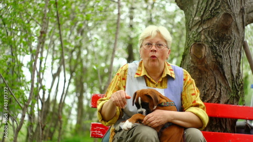 35mm camera - senior woman enjoying in nature with a German Boxe