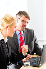 Businesspeople looking at laptop in consultation