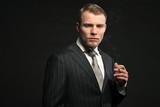 Fashion man in suit smoking cigarette. Studio shot.