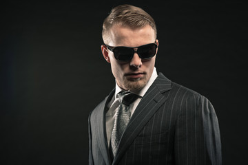 Fashion man in suit wearing sunglasses. Studio shot.