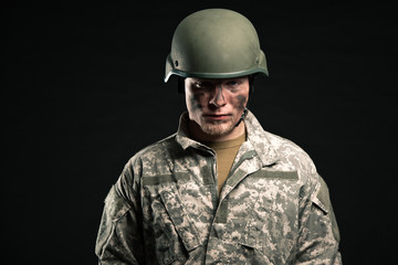 Military young man wearing helmet. Studio portrait.