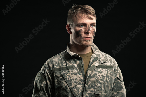 Military young man with camouflage on face. Studio shot.