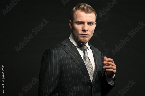 Fashion man in suit smoking cigarette. Studio shot.