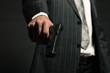 Man in suit shooting with gun. Studio shot against black.