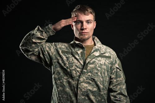 Military young man salutes. Studio portrait.