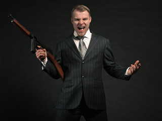 Man in suit shooting with rifle. Studio shot against black.