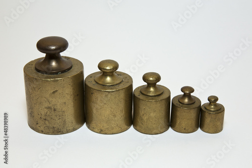 Five old calibration weights in a row and isolated on white
