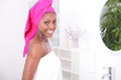 Woman stood in bathroom wearing towel