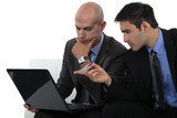 duo of businessmen with laptop interacting