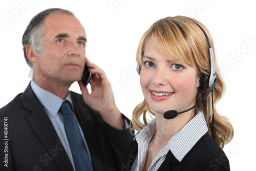 Woman in a headset next to a man with a cellphone