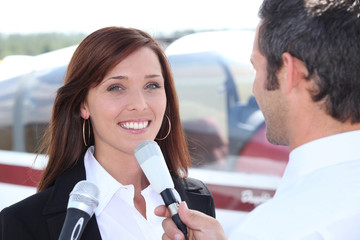 Reporter interviewing woman in airport