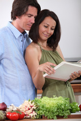 Couple watching cookbook in a kitchen