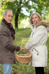 Couple walking through field with basket