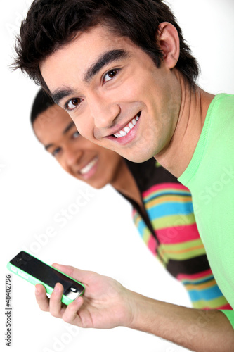 Two male teenagers reading text message
