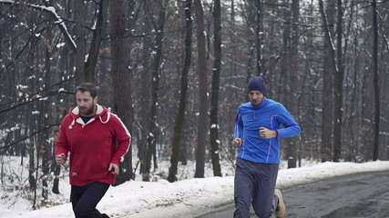 Two men jogging in the forest in winter, crane shot