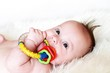 The baby plays a rattle (3,5 months)