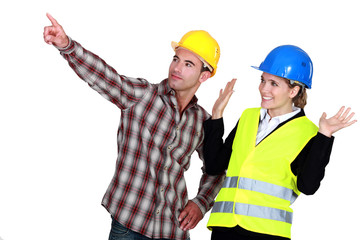 Construction worker pointing a problem while his co-worker