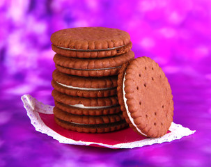 Chocolate cookies with creamy layer on purple background