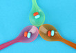 Plastic spoons with color pills on blue background