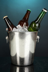Beer bottles in ice bucket on darck blue background