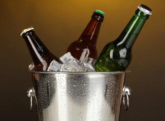 Beer bottles in ice bucket on darck yellow background