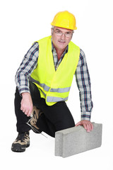 mature bricklayer with concrete block and trowel