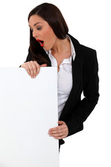 Shocked businesswoman stood with blank poster