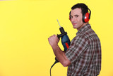Man with drill and earmuffs