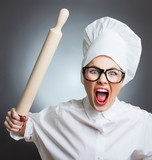 Angry woman cook trying to hit with a rolling pin over a gray
