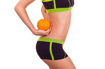 Slim figure of girl in a sportwear with orange in a hand