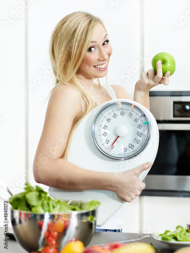 Smiling girl in the kitchen is proud of her healthy diet