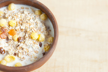 bowl of oat cereal with milk on a wooden surface