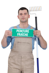 painter holding fresh paint sign and roller